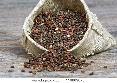 Lentils In Small Hessian Bag On Wooden Table