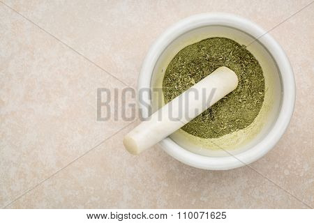 dried stevia leaves crushed in a mortar - natural sweetener, sugar substitute