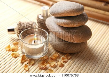 Beautiful composition with candle, aroma oil and pebbles on bamboo mat