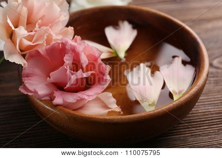 Pink rose and petals in a bowl of water on wooden background