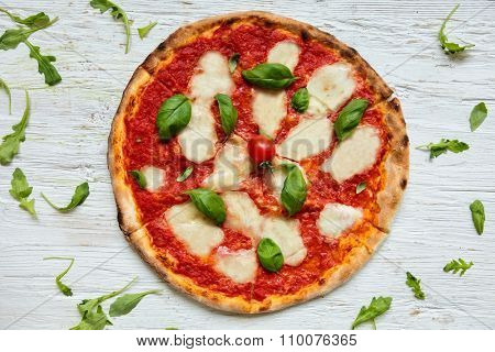 Delicious italian pizza served on wooden table, shot from above