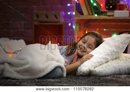 Pretty little girl laying on the pillow under soft plaid in Christmas decorated room