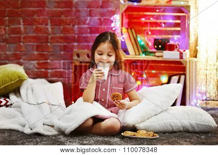 Pretty little girl with glass of milk and tasty cookies in Christmas decorated room