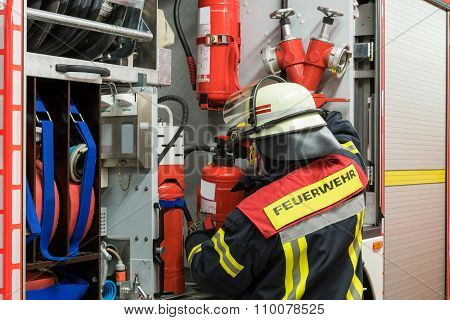 German Firefighter in action and gets a fire extinguisher from the emergency vehicle
