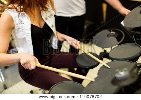 music, sale, people, musical instruments and entertainment concept - close up of man and woman playing on drum kit