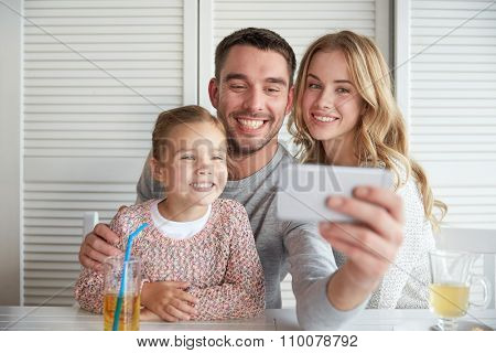 family, parenthood, technology and people concept - happy mother, father and little girl having dinner and taking selfie by smartphone at restaurant