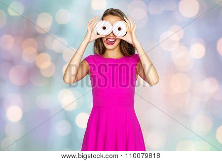 people, holidays, junk food and fast food concept - happy young woman or teen girl in pink dress having fun, looking through donuts and showing tongue over holidays lights background