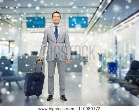 business trip, traveling, luggage and people concept - happy businessman in suit with travel bag over airport background and snow effect