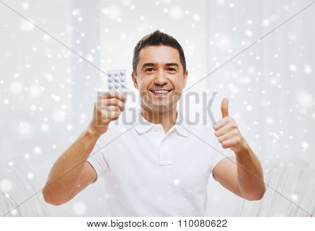 people, medication, medicine and health care concept - happy man showing thumbs up and holding pack of pills at home over snow effect
