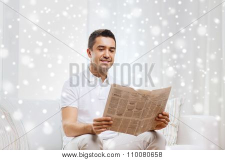 leisure, information, people and mass media concept - happy man reading newspaper at home over snow effect
