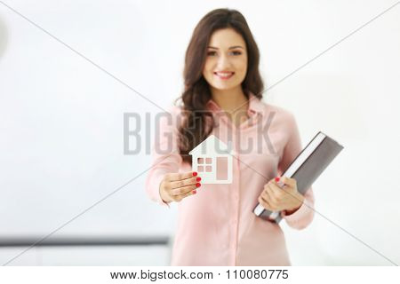 Friendly female estate-agent on light background