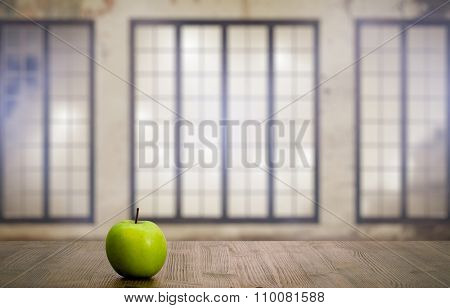 green apple on vintage wooden table in old room with big windows