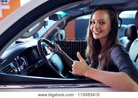 Beautiful young happy woman in car. Attractive  smiling caucasian girl sitting in white auto. pretty female person driving big car suv