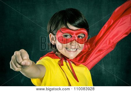 Closeup of little boy in superhero costume posing isolated on blackboard. Smiling kid looking at camera with red mask. Cheerful boy wearing superhero costume with red cape flying with closed fist.