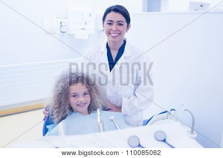 Pediatric dentist smiling with little girl in the chair at the dental clinic