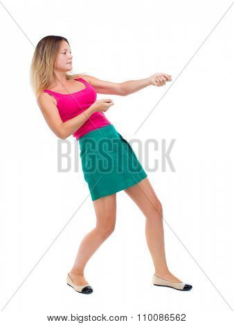 back view of standing girl pulling a rope from the top or cling to something. girl  watching.  Isolated over white background. The blonde in a green skirt and pink blouse pulling a rope over.
