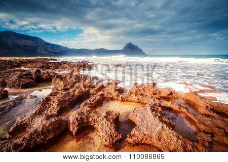 Fantastic view of the nature reserve Monte Cofano. Dramatic morning scene. Dark overcast sky. Location cape San Vito. Sicilia, Italy, Europe. Mediterranean and Tyrrhenian sea. Beauty world.