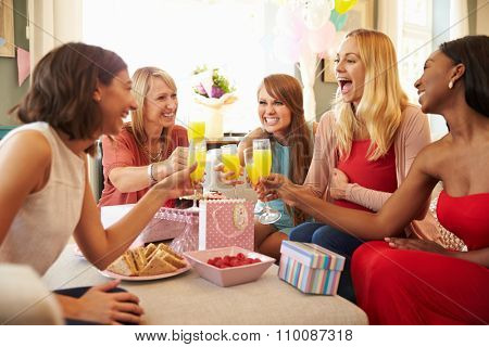 Friends Making A Toast With Orange Juice At Baby Shower
