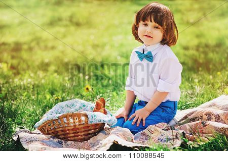 cute dressy long hair toddler boy on summer picnic with basket of sweets sitting on blanket