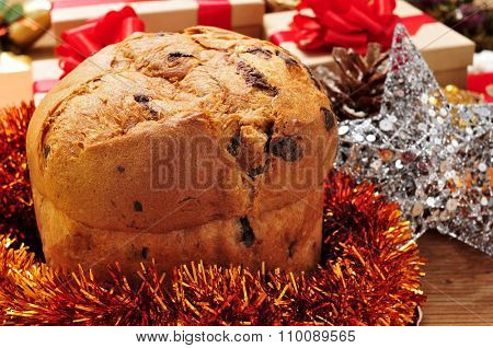 closeup of a panettone, a typical Italian sweet for Christmas time, on a table with some gifts, tinsel and some christmas ornaments