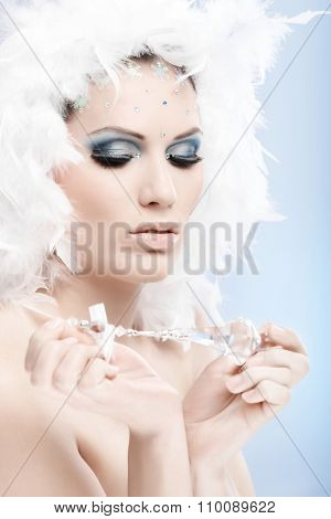 Artistic photo of beautiful winter girl holding crystal gem, wearing fancy makeup with strasses and white feather hat. Looking down.
