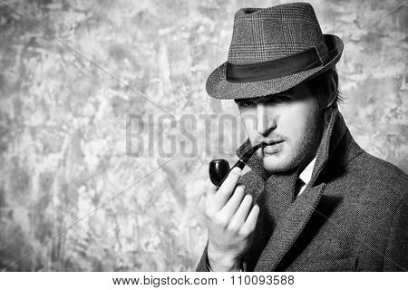 Handsome young man wearing classic hat and a coat smokes a pipe. Beauty, fashion.