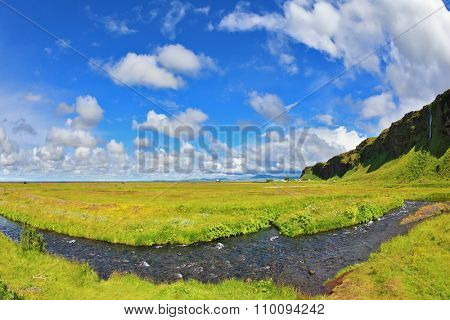 Iceland in July. Green fields and streams in warm summer day