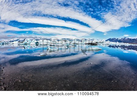 Ice lagoon in Iceland. Magnificent summer morning in the ocean gulf with floating ice floes. The layered clouds fanning are reflected in a smooth surface of water