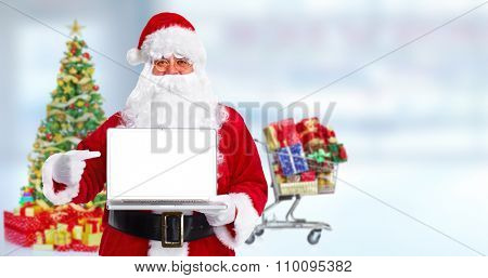 Happy traditional Santa Claus with laptop computer over blue background.