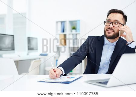 Handsome employer speaking on the phone in office