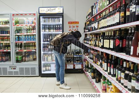 MOSCOW, RUSSIA  -  APRIL 07, 2015: Supermarket Pyaterochka with the most affordable prices. Russia's largest retailer. Woman choosing a bottle of wine in supermarket store Pyaterochka.