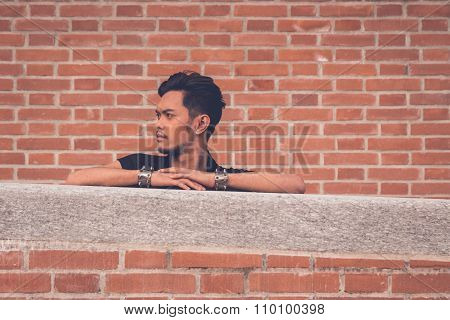 Handsome Asian Model Posing With A Brick Wall In Background