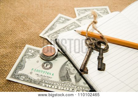 Opened Notebook, Pencil, Keys And Money On The Old Tissue