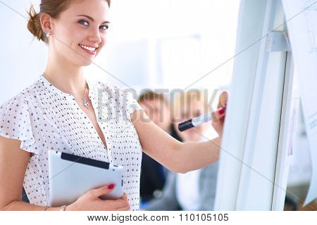 Businesswoman writing on flipchart while giving presentation to colleagues in office