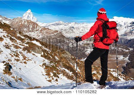Hiker takes a rest admiring the Matterhorn peak. Sunny day, early winter. Matterhorn Massif, Valle d'Aosta, Italy, Europe.