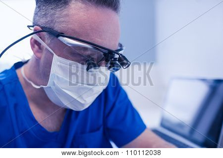 Concentrated male dentist with dental loupes in clinic