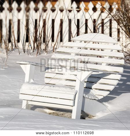 A round back Adirondack chair fondly know as a moon chair in the winter garden.