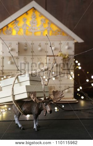 Toy moose carrying gift with wooden house in background