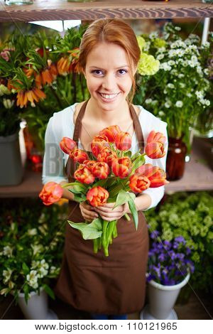 Young beautiful female florist holding bouquet of tulips