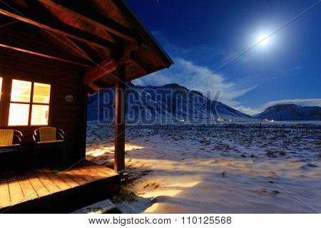 Cottage on a background of mountains in the moonlight. South Iceland. Travel concept