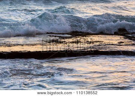 Ocean Waves Splash Over Calm Rock Shelf At Dawn