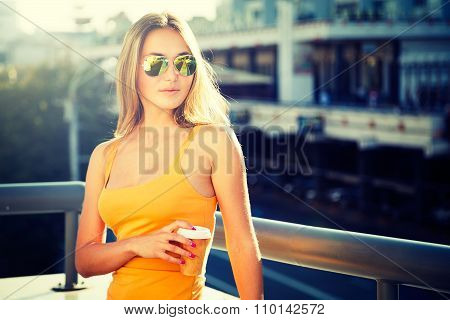 Young Fashion Woman with Coffee to Go in the City