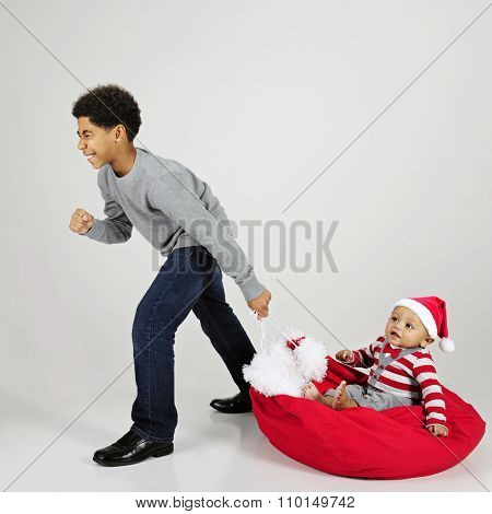 An elementary boy struggling to give his baby brother a ride on Santa's sack.  On a gray background.
