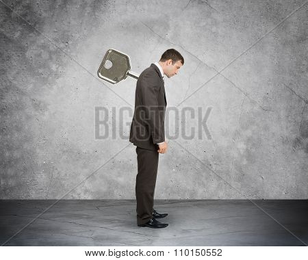 Businessman with key in back on grey