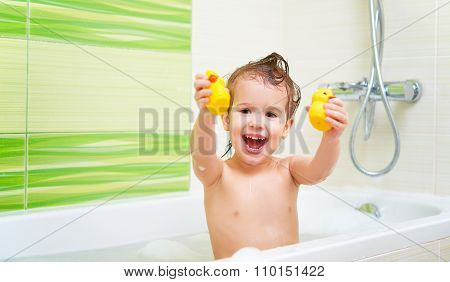 Happy Child With Yellow Duck Toys Bathes In  Bath With Foam And Bubbles