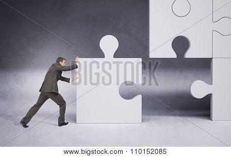 Businessman pushing grey puzzle piece