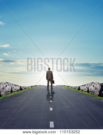 Businessman in suit walking on road with mountains
