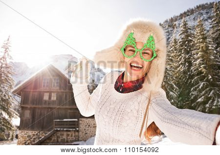 Woman In A Christmas Glasses Taking Selfie Near A Mountain House