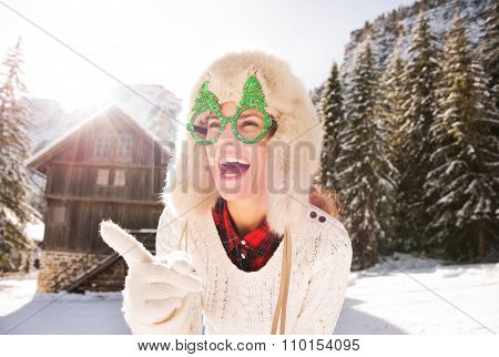 Woman In Christmas Glasses Pointing On Something In Countryside