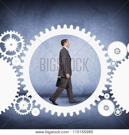 Businessman walking in cog wheel
